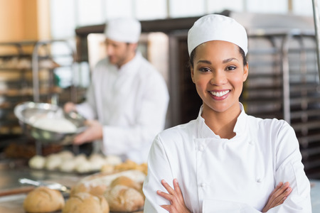 restaurant kitchen: Pretty baker smiling at camera in the kitchen of the bakery Stock Photo