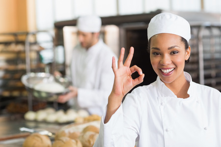 career young: Pretty baker smiling at camera in the kitchen of the bakery Stock Photo