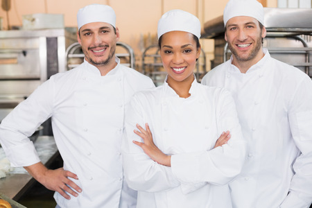 bakery store: Team of bakers smiling at camera in the kitchen of the bakery