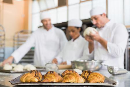 panadero: Equipo de panaderos que trabajan en el mostrador en la cocina de la panadería