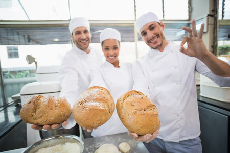 restaurant staff: Team of bakers smiling at camera holding bread in the kitchen of the bakery