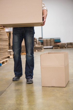low section: Low section of worker carrying box in the warehouse