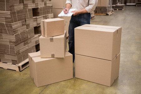 inventory: Warehouse worker checking his list on clipboard in a large warehouse