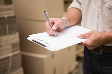 inventories: Warehouse worker checking his list on clipboard in a large warehouse