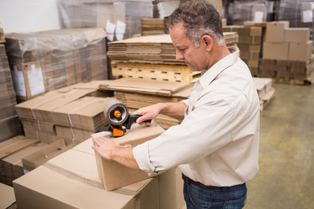 sealing tape: Warehouse worker preparing a shipment in a large warehouse