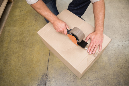sealing tape: Close up of warehouse worker preparing a shipment in a large warehouse