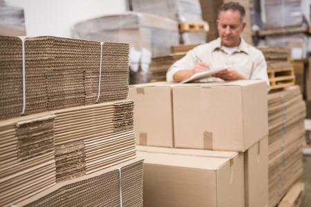 inventario: Trabajador del almac�n que comprueba su lista en el portapapeles en un gran almac�n