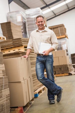 packaging: Smiling warehouse worker leaning against boxes in a large warehouse