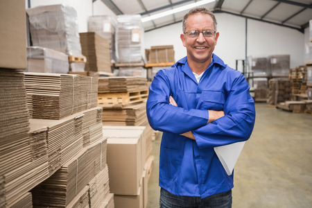warehouse: Smiling warehouse manager standing with arms crossed in a large warehouse Stock Photo