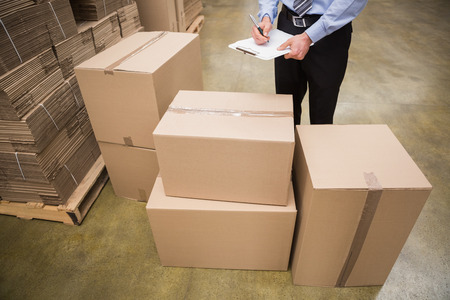 warehouse: Warehouse worker checking his list on clipboard in a large warehouse