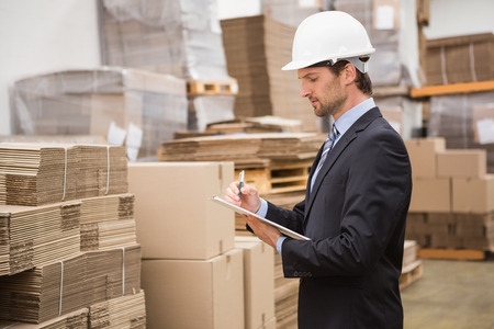 Serious warehouse manager checking inventory in warehouse Stock Photo
