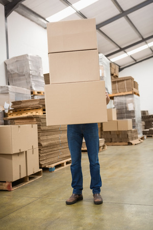obscured: Obscured worker carrying boxes in the warehouse