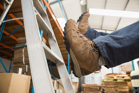 ladder: Low section of worker falling off ladder in the warehouse Stock Photo