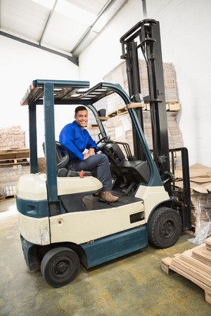 forklift driver: Portrait of driver operating forklift machine in warehouse