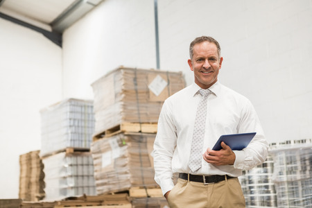 pocket pc: Manager standing with hand in the pocket holding tablet pc in a large warehouse Stock Photo