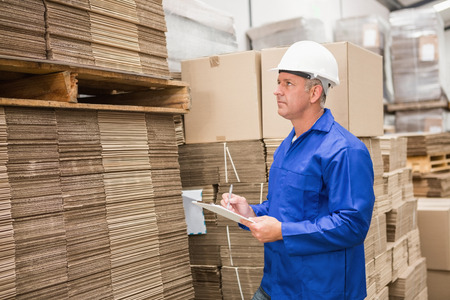 Warehouse worker checking his list on clipboard in a large warehouse photo