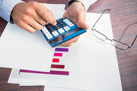 figuring: Close up of finger using calculator at desk in a large warehouse