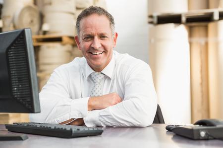 hombres trabajando: Encargado sonriente con los brazos cruzados sentado en el escritorio en un gran almac�n