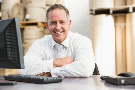 Smiling manager with arms crossed sitting at desk in a large warehouse Stok Fotoğraf