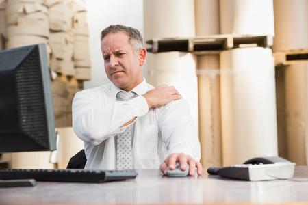 dolor hombro: Jefe de almac�n que sufren de dolor de hombro en un gran almac�n Foto de archivo