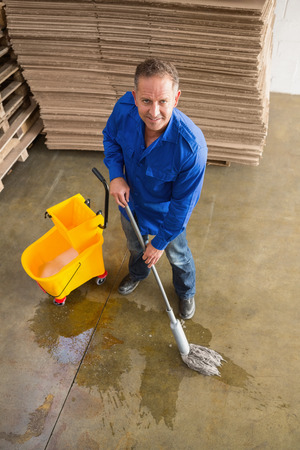 superintendent: Portrait of smiling man moping warehouse floor