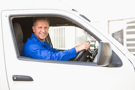 Hombre de salida sonriente conduciendo su camioneta fuera del almacén Foto de archivo