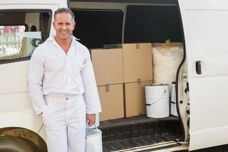 redecorating: Painter smiling leaning against his van outside the warehouse