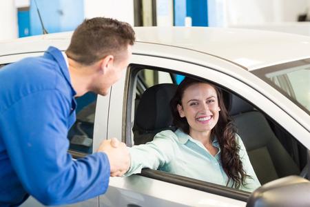 mecanico: Cliente estrechando la mano de mec�nico en el garaje de reparaci�n