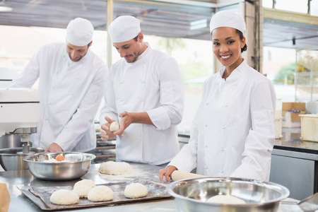 baker: Team of bakers working at counter in the kitchen of the bakery Stock Photo