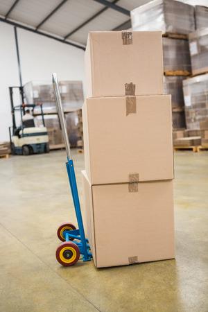 cajas de carton: Cajas de cart�n en la carretilla en almac�n