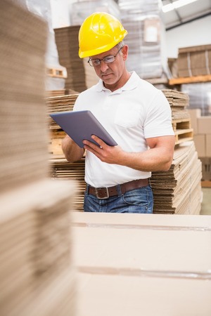 Warehouse worker using digital tablet in warehouse photo