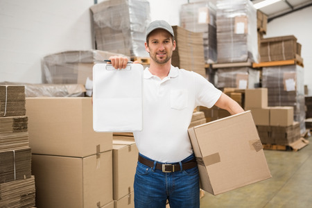 loading bay: Portrait of smiling delivery man with box and clipboard in warehouse Stock Photo