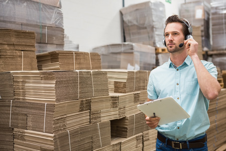 warehouse: Warehouse worker wearing a headset holding clipboard in a large warehouse