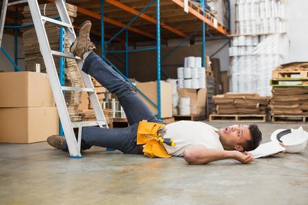 accidente trabajo: Vista lateral del trabajador de sexo masculino tendido en el suelo en almac�n Foto de archivo