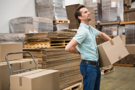 man back pain: Side view of worker carrying box in the warehouse Stock Photo