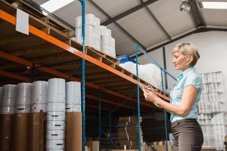 warehouse: Warehouse manager checking her list on clipboard in a large warehouse Stock Photo