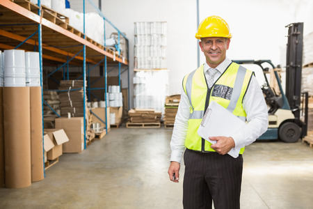 Warehouse manager wearing hard hat holding clipboard in a large warehouse