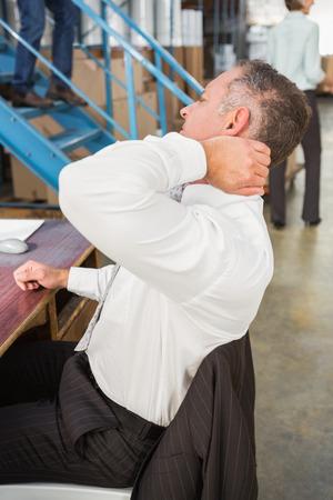 dolor muscular: Vista lateral del encargado del almac�n que usa el ordenador en el almac�n