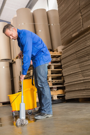superintendent: Portrait of focused man moping warehouse floor