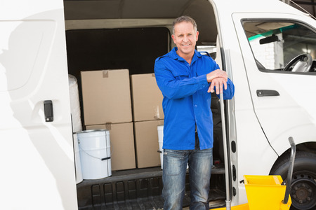 superintendent: Cleaning agent standing and smiling at camera in front of his van Stock Photo