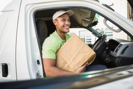 loading bay: Smiling delivery driver in his van holding parcel outside warehouse Stock Photo