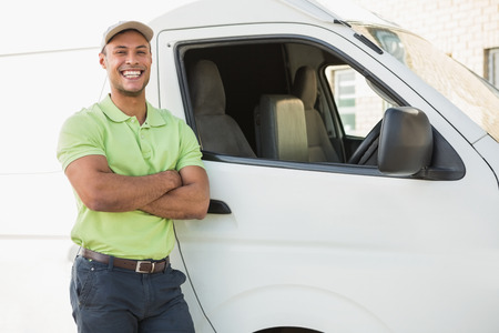 delivery service: Three quarter length portrait of smiling man standing against delivery van Stock Photo