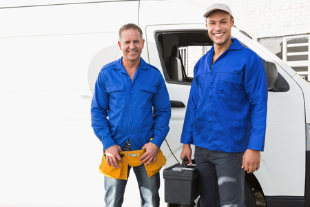 handyman tools: Smiling handymen looking at camera in front of their van Stock Photo