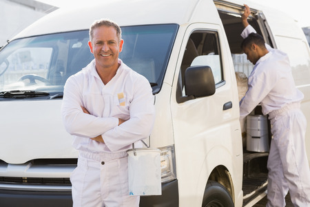 pintor: Pintor sonriente apoyado en su camioneta fuera del almac�n