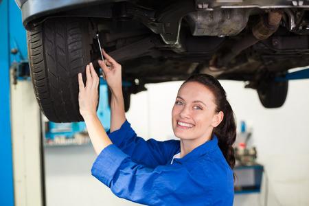 mecanico: Mec�nico sonriente ajustar el neum�tico en el garaje de reparaci�n Foto de archivo