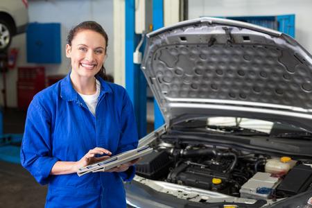 mecanico: Mec�nico que usa la tableta para fijar coche en el garaje de reparaci�n