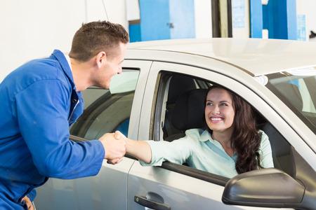 garage automobile: Serrant la main avec m�canicien au garage de r�paration client