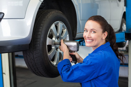 young female: Mechanic adjusting the tire wheel at the repair garage Stock Photo