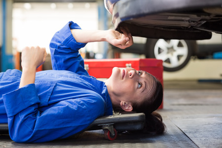 female worker: Mechanic lying and looking under car at the repair garage Stock Photo