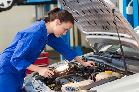 Mechanic examining under hood of car with torch at the repair garage Stok Fotoğraf